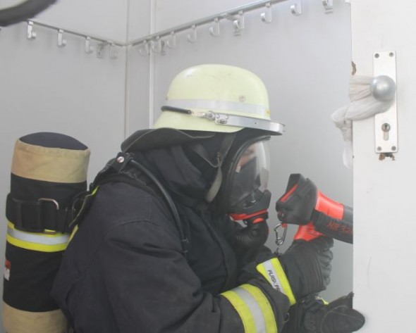 Ein Feuerwehrmann kontrolliert einen Raum durch den Türspalt mit dem Würfelblick.
