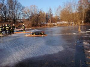 Korrekte Eisrettung der Feuerwehr. Mit Leiter zur Vergrößerung der Auflagefläche und gesichert mit einem Seil