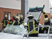 Die Einsatzkräfte klappen das Dach des PKW nach hinten